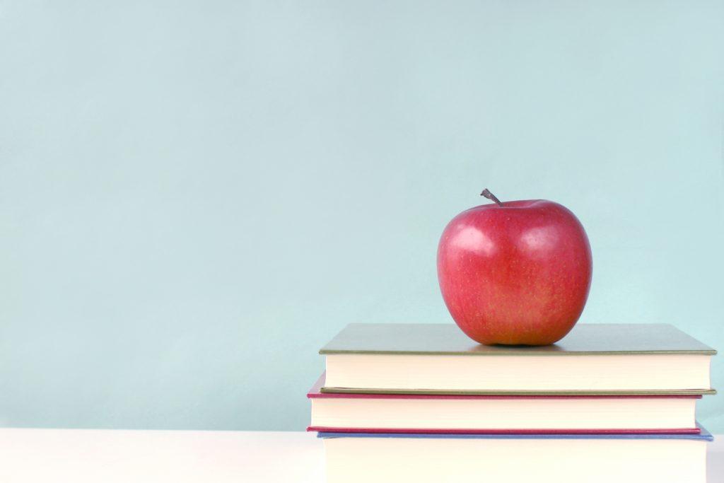 積み上げられた本の上の林檎